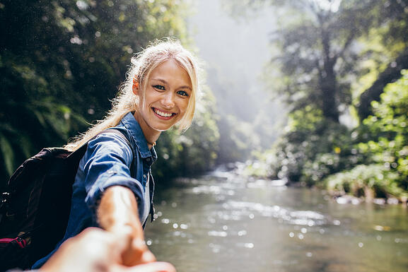 Woman offering hand on river